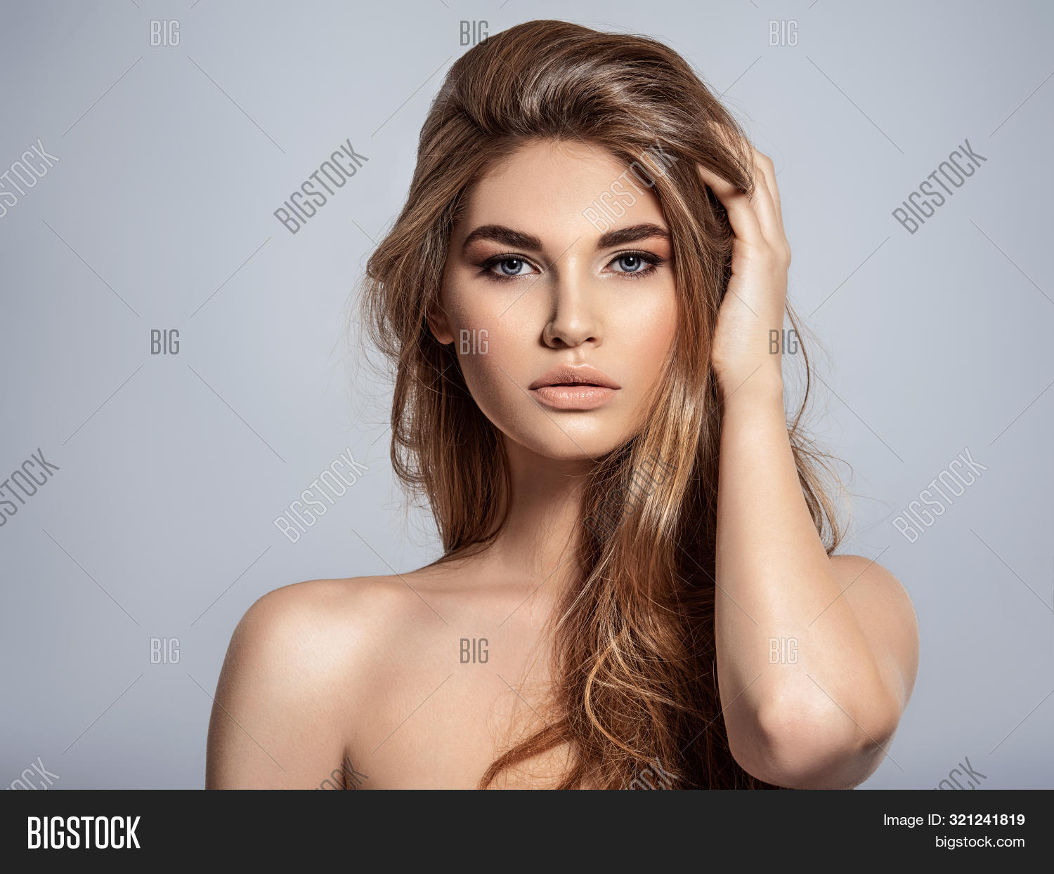 Woman with beauty long brown hair and natural makeup.  Beautiful face of an attractive  model with blue eyes. Closeup portrait of a caucasian female. Attractive fashion model.