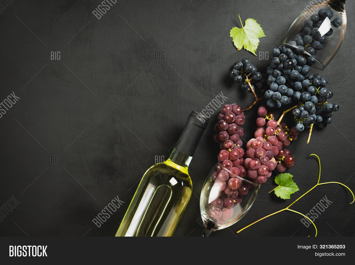 White wine bottle, wineglasses, fresh grapes and leaves on black wood background. Flat lay, top view, copy space. Wine bar, winery, wine tasting concept