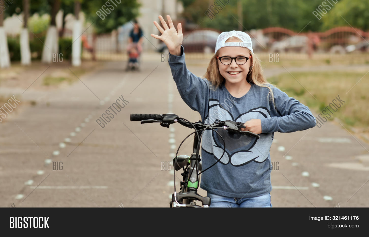 An eleven-year-old girl in a good mood rides a bicycle and after a stop shows a thumbs-up.
