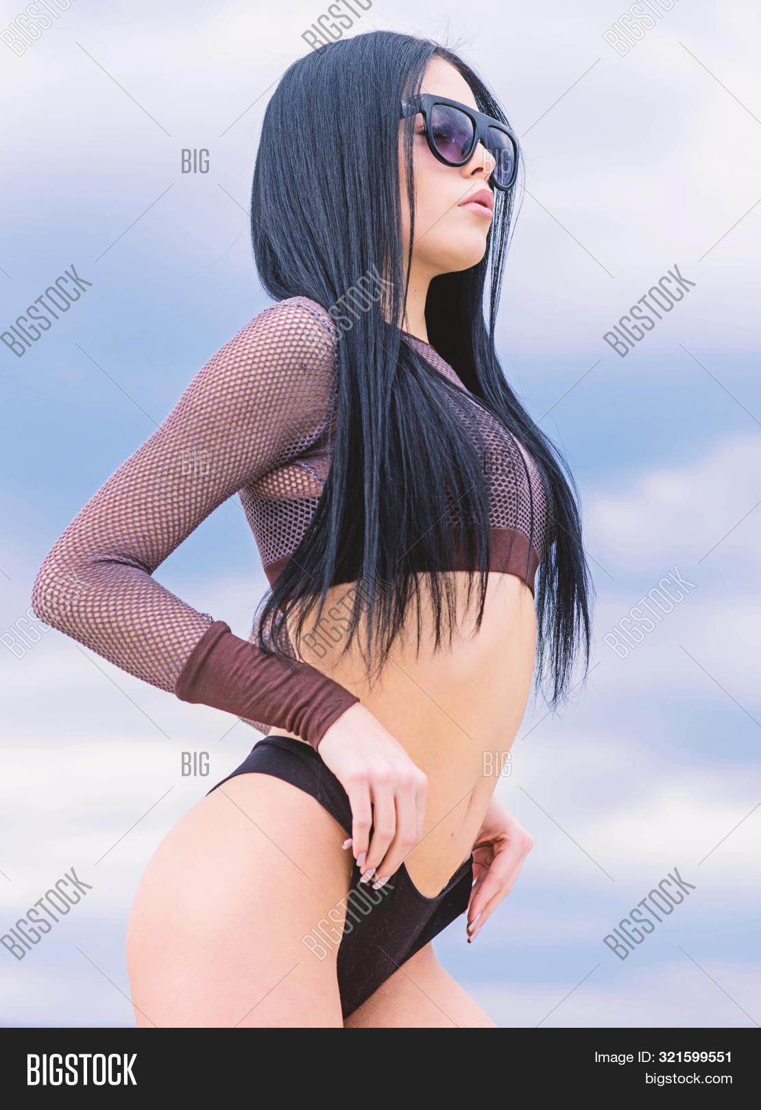 Girl Attractive Sexy Body Posing Sky Background. Woman Wear Sunglasses And Bikini. Slim Waist And Lo