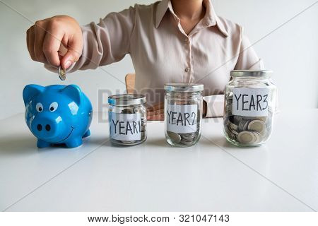Business woman putting coin into blue piggy bank with 3 years planing account , step up growing business to success and saving for retirement  concept. stock photo