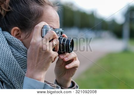 Young brunette woman in gray scarf taking pictures with retro photo camera on street. stock photo