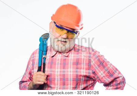 carry out repairs. man builder with adjustable pipe wrench. professional repairman in helmet with gas wrench. architect repair and fix. engineer worker. build and construction. mature bearded man. stock photo