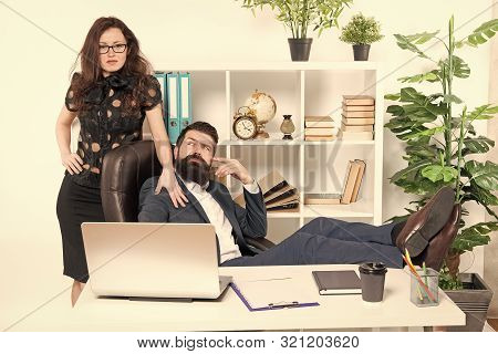 Lazy boss office. Offer massage. Man bearded hipster boss sit in leather armchair office interior. Boss and secretary girl at workplace. Relations at work. Business people and staff concept. stock photo