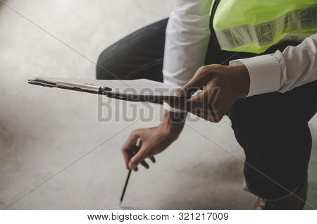 Construction. young foreman builder, engineer or inspector checking and inspecting concrete floor at construction site building interior before complete new project, contractor and engineering concept stock photo