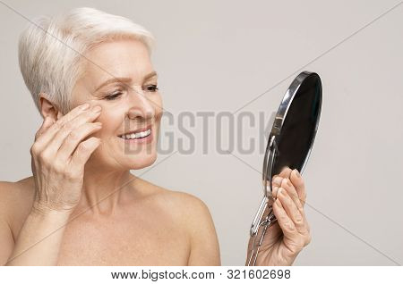 Beautiful senior lady looking at mirror and applying anti-aging cream, copy space stock photo