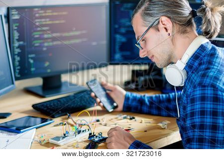 Developer is connecting breadboard to microcontroller. Man is holding smartphone with program code software for controlling electronic device. Chips, resistors, diodes on desktop of hardware engineer. stock photo