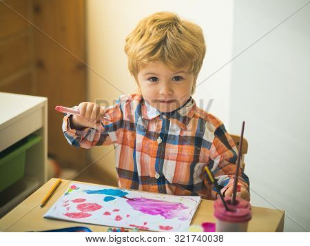 Boy is painting a picture. A beautiful child with felt-tip pens sits at the table and is engaged in creativity and art. Drawing in kindergarten, Childrens development, Art therapy for children. stock photo