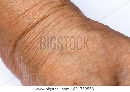 Senior woman's wrinkled wrist of the arm on white background, Close up & Macro shot, Selective focus, Asian Body skin part, Healthcare concept, Abstract background stock photo
