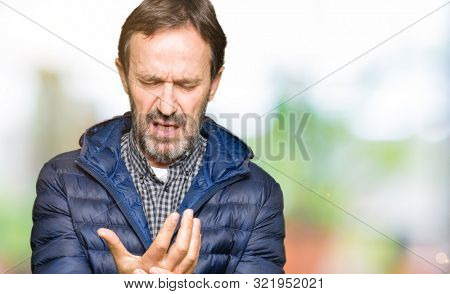 Middle age handsome man wearing winter coat Suffering pain on hands and fingers, arthritis inflammation stock photo