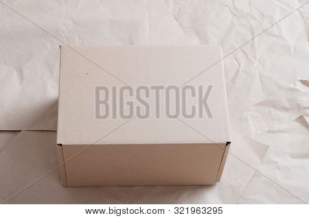 Pile of rumpled kraft paper lying in disorder on a wooden floor stock photo