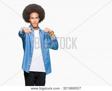 Young african american man with afro hair Punching fist to fight, aggressive and angry attack, threat and violence stock photo