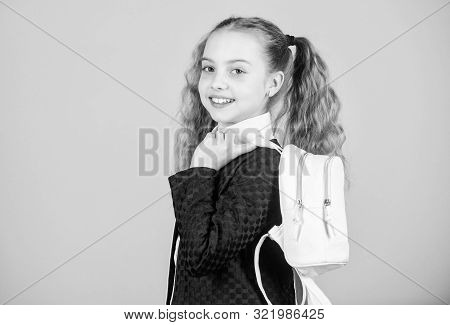Learn how fit backpack correctly. Girl little fashionable cutie carry backpack. Popular useful fashion accessory. Schoolgirl ponytails hairstyle with small backpack. Carrying things in backpack stock photo