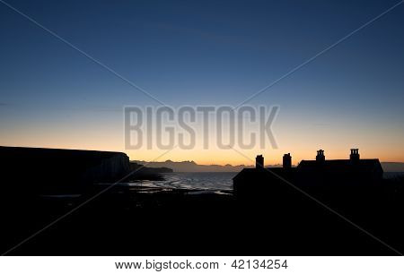 Winter sunrise behind coastguard cotages at Seaford Head with Seven Sisters cliffs in background stock photo