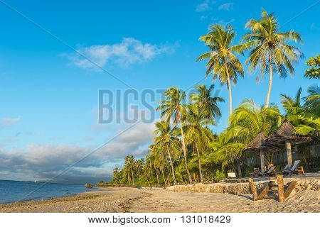 Tropical beach background from Anda White Beach at Bohol island with beach chairs on the white sand