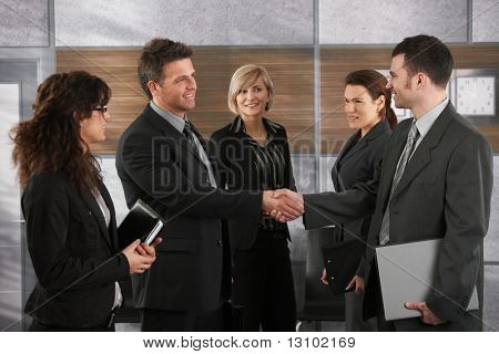 Happy businesspeople shaking hands greeting each other before business meeting in office. stock photo