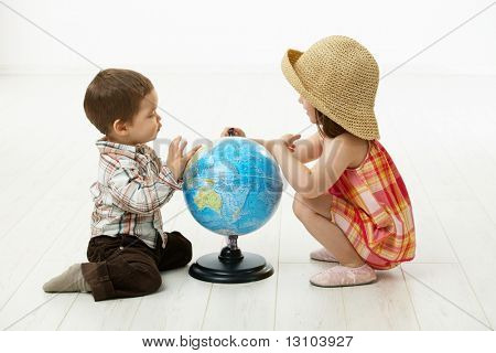 Little kids crouching on floor playing with globe over white background. stock photo
