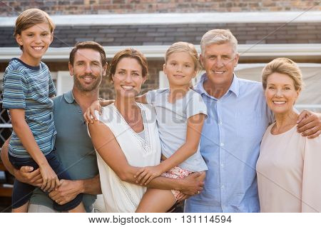 Portrait of cheerful extended family standing outside their house. Happy family standing outside and