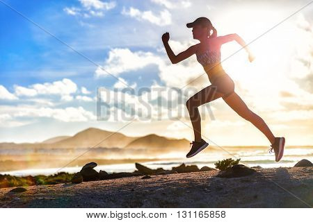 Athlete runner trail running on summer beach. Fit body silhouette of sports Woman in sportswear cap
