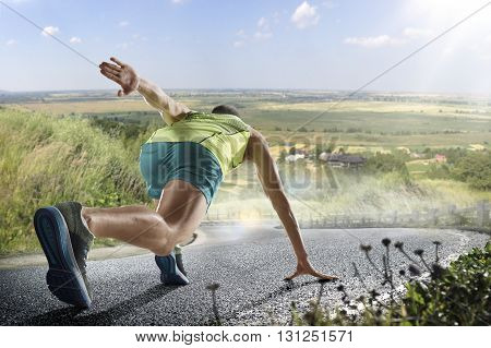 Running athlete man. Male runner sprinting during outdoors training for marathon run. Athletic fit young sport fitness model in his twenties in full body length on road outside in nature.