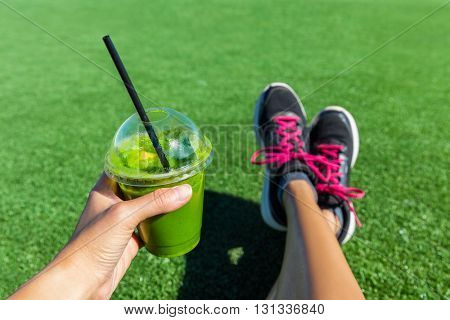 Green smoothie woman drinking plastic cup breakfast takeaway juice to go after morning run in summer