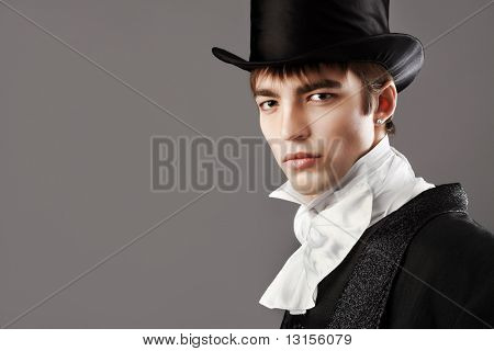 Portrait of a young gentlemen wearing dinner jacket and black top hat. Shot in a studio. stock photo