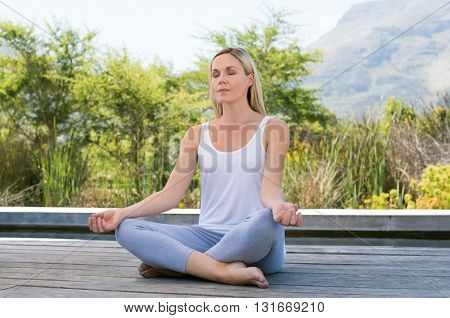 Woman practicing yoga and meditating outdoors. Mature woman relaxing with lotus yoga position in the