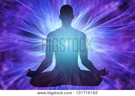 Silhouette of man in meditation and surrounded by rays of light and energy