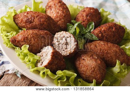 Delicious spicy Kubbeh with bulgur onion and pine nuts on a plate macro. horizontal stock photo