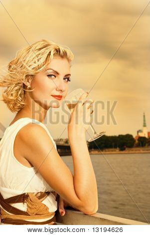 Beautiful blond girl drinks champagne near the river at sunset time stock photo