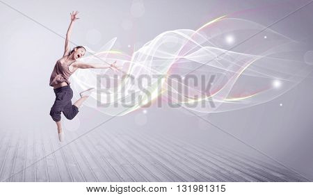 A beautiful young hip hop dancer dancing contemporary urban street dance in front of grey wall backg