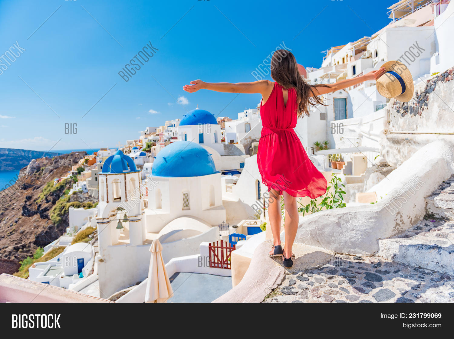 Europe travel vacation fun summer woman dancing in freedom with arms up happy in Oia, Santorini, Gre
