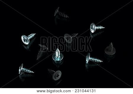 silver chrom and anodized screws on black background stock photo