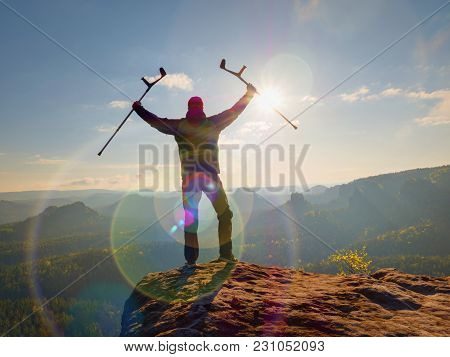 Be winner. Man tourist after accident use knee brace features  and forearm crutches. Man looking over valley to Sun hang at horizon. stock photo