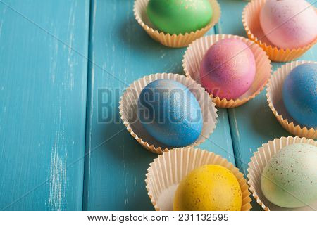 Clorful easter eggs on blue rustic wooden background. Mockup for greeting card to spring holiday, closeup, copy space stock photo