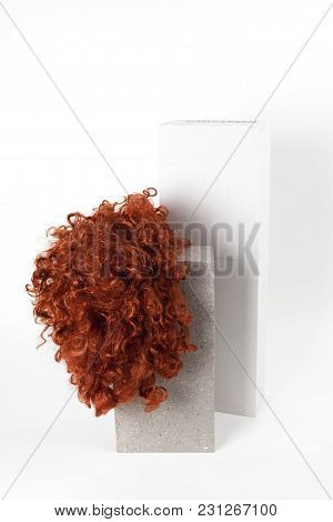 A red wig put on a gray cinderblock, on a white background. Minimal funny and quirky design still life photography stock photo