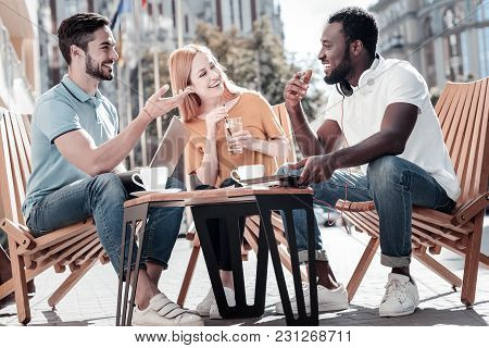 Never getting bored together. Three young mates grinning broadly while enjoying a pleasant conversation and joking outdoors. stock photo