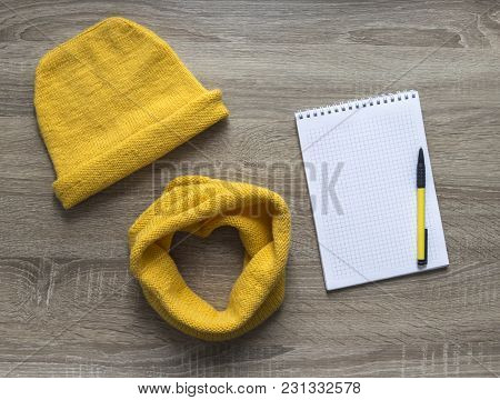 background tree yellow snood scarf cap with spell knitted knitting needles face mohair merino wool acrylic yarn notepad pen stock photo