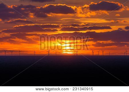 Sunset At Wind Turbines Windmills Offshore Clean Power Farm Far. Many Energy Stations On Sea Water,