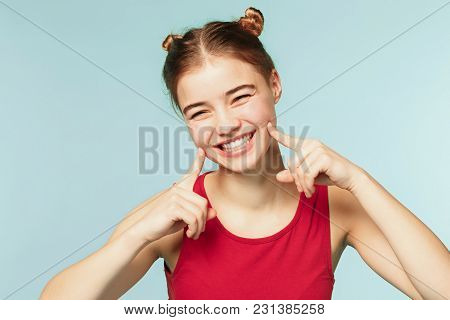 Woman Smiling With Perfect Smile On The Pink Studio Background. Pretty Young Girl. She Is Smiling Wi