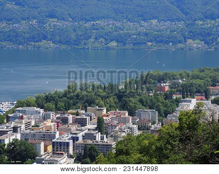 Panoramic view of swiss travel city of LOCARNO in SWITZERLAND and landscapes of alpine Lake Maggiore with yacht haven and Alps slopes in 2017 warm sunny summer day, Europe on July. stock photo