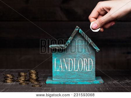 Wooden house model with coins next to it and hand holding the coin with conceptual text. Landlord stock photo