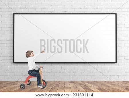 Cute little boy in a white shirt and dark blue jeans is riding a tricycle and showing with his finger. A wooden floor room with concrete walls. A blank whiteboard. Mock up stock photo