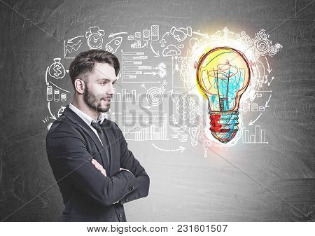 Side view of a pensive young businessman with a beard. He is wearing a suit and a tie and standing with crossed arms. A blackboard with an idea sketch stock photo