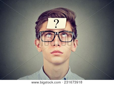 thinking man with question mark looking up on gray wall background stock photo