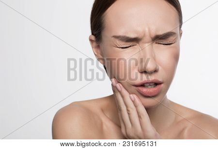 Portrait of unhappy girl is standing and holding her hand on cheek with closed eyes while wincing her face in terrible toothache. Isolated background and copy space in the left side stock photo