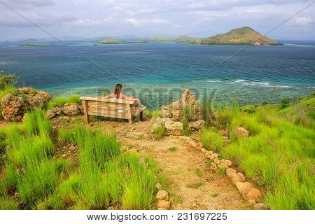 Young woman sitting on a bench at the viewpoint on Kanawa Island in Flores Sea, Nusa Tenggara, Indonesia. Kanawa Island is within the Komodo National Park. stock photo