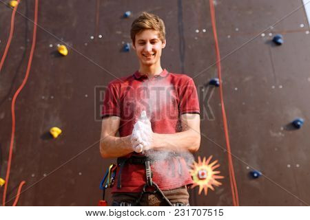 Close up of climber man coating hands in powder chalk magnesium and preparing to climb outdoor training rock wall. stock photo