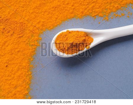 Turmeric Powder or Curcuma longa and white spoon with turmeric powder on gray background. Top view. Copy space for text. stock photo