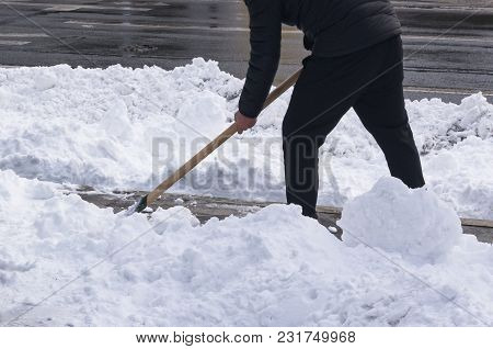 Cleaning the snow with a shovel after a heavy snowfall. A man removes snow on a city street stock photo